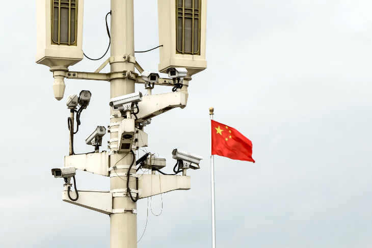 Surveillance cameras in Beijing, China with Chinese flag waving in background